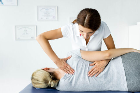 attractive chiropractor touching hand of patient in grey t-shirt